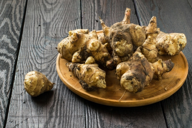 55032478 - fresh organic jerusalem artichoke (helianthus tuberosus) with soil particles on a round wooden board
