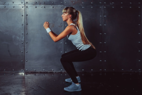 43880639 - athletic young woman fitness model warming up doing squats exercise for the buttocks concept sport slimming healthy lifestyle.