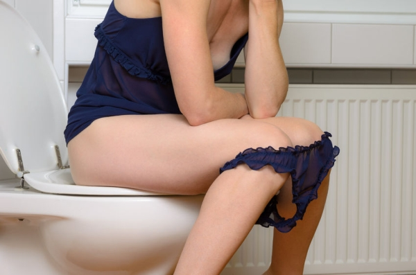 59847977 - young woman in underwear sitting on a toilet with her blue panties around her knees in a close up side view of her body