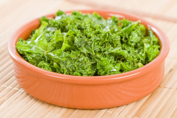 49521807 - curly kale - cooked cale in an earthenware dish.
