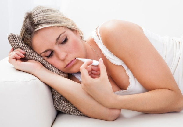 21478234 - young sick woman with a thermometer in her mouth