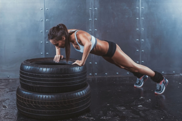 40037451 - sportswoman. fit sporty woman doing push ups on tire strength power training concept crossfit fitness workout sport and lifestyle