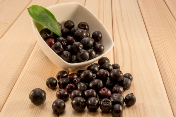 61470110 - white bowl full with fresh and tasty aronia spilled on wooden table