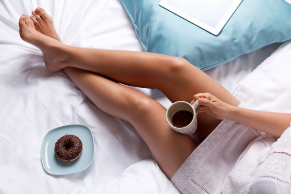 46598261 - woman having donut and coffee for breakfast in the bed