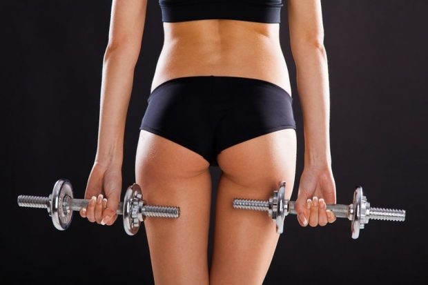17899983 - slim woman with dumbbells, black background