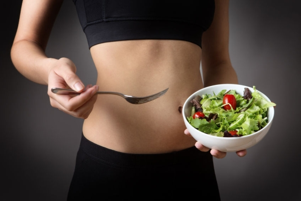 56629784 - close up studio shot of a young sporty woman wearing her gym kit, holding a bowl of healthy salad