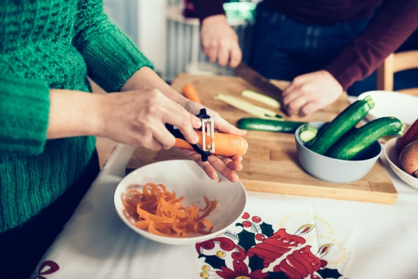 50209955 - close up on the hands of young handsome caucasian woman peeling carrots for dinner, man cutting vegetables too on the background - healthy, veggie, food concept