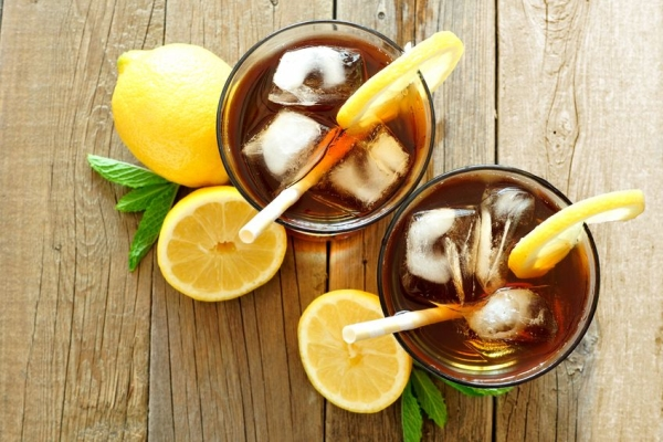 59407530 - two glasses of iced tea with lemon, overhead view on a rustic wooden background