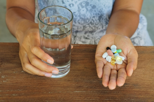 48538969 - medicines and glass of water in woman hand. medicine and woman. woman took so much medicine.