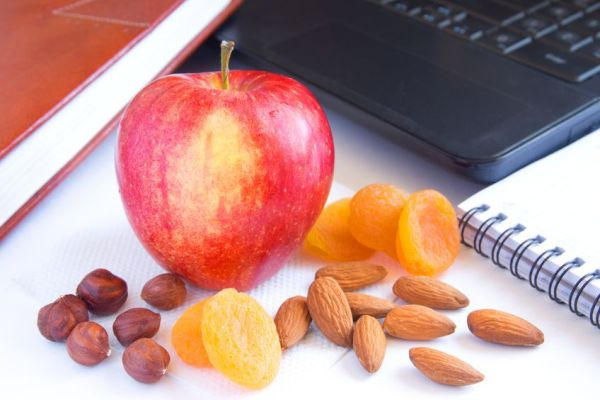 19318136 - healthy quick snack (lunch) in office. red apple, dry fruits (apricots) and nuts on desk with computer and planner.