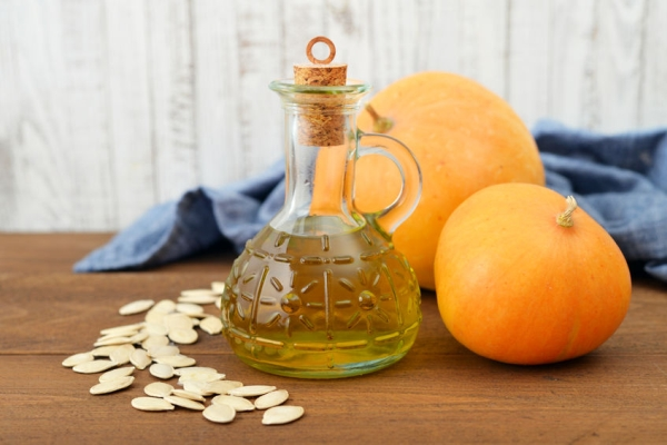 31827744 - pumpkin seed oil in bottle with seeds and pumpkin on wooden background