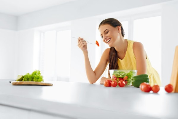 48201519 - healthy diet. beautiful smiling woman eating fresh organic vegetarian salad in modern kitchen. healthy eating, food and lifestyle concept. health, beauty, dieting concept.