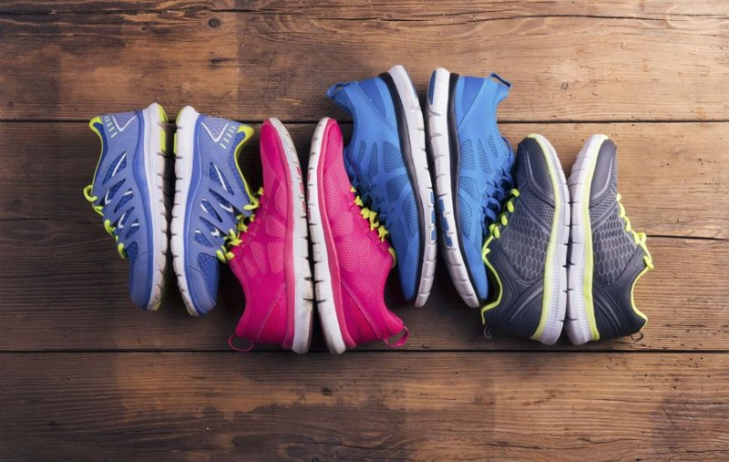 39230335 - four pairs of various running shoes laid on a wooden floor background