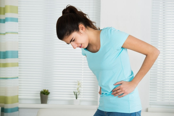 51726203 - young woman suffering from stomach ache standing at home