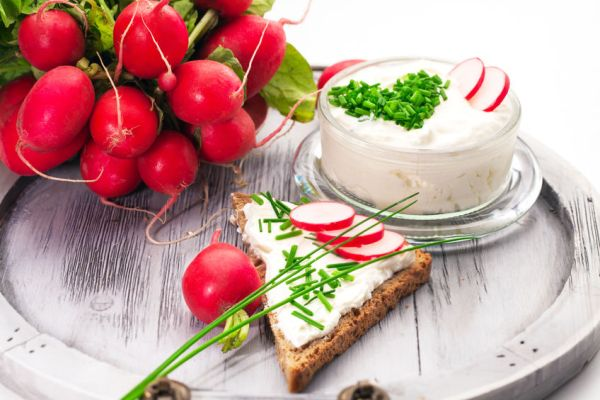 38767434 - a bowl with curd and radish and a heart shaped chives decoration and brown bread