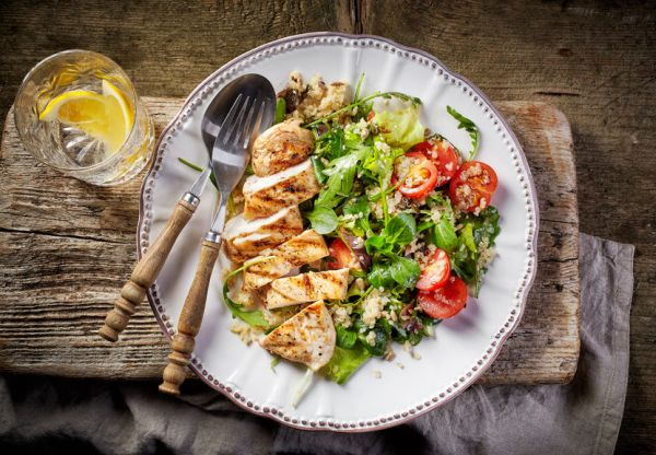 50860912 - quinoa and vegetable salad and grilled chicken fillet on white plate, top view
