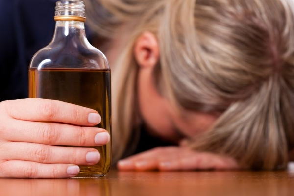 10899500 - woman sitting at home drinking way too much brandy, she is addicted