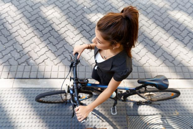 60588849 - young woman in business wear commuting on bicycle in city