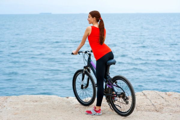 40831457 - sport woman in red shirt standing with bicycles on the concrete seacoast