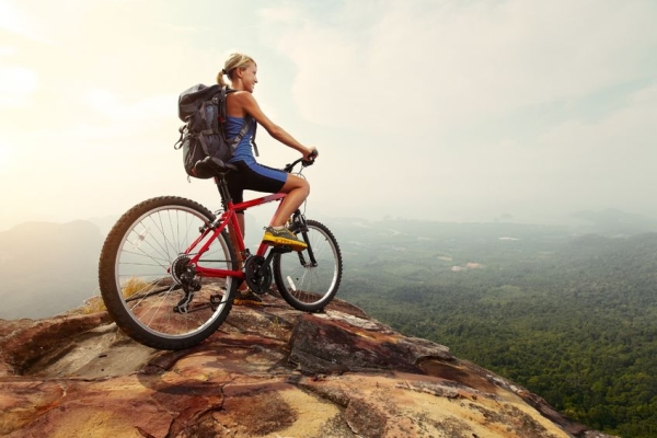 19872938 - young woman athlete standing on top of a mountain with red bicycle and enjoying valley view