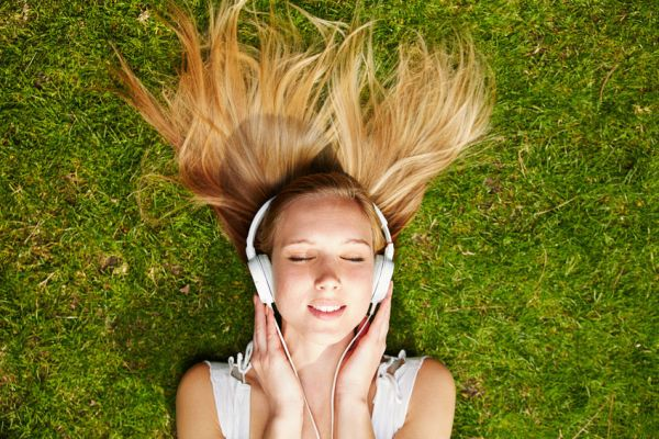 38856779 - girl listening to music streaming with headphones in summer on a meadow