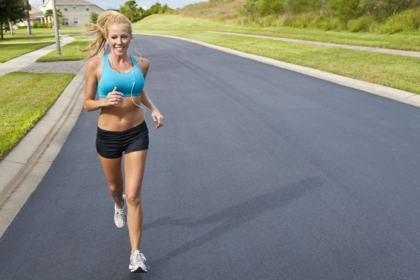5839638 - a beautiful fit and healthy blond woman road running while listening to music on her portable mp3 player