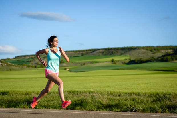 43152951 - sporty woman running fast on country side road. female athlete training outdoor.