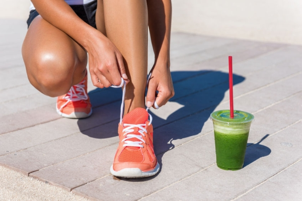 65499222 - running woman athlete runner getting ready for beach morning run by tying shoe laces of running shoes with green vegetable smoothie breakfast. closeup on feet. fitness and healthy lifestyle concept.