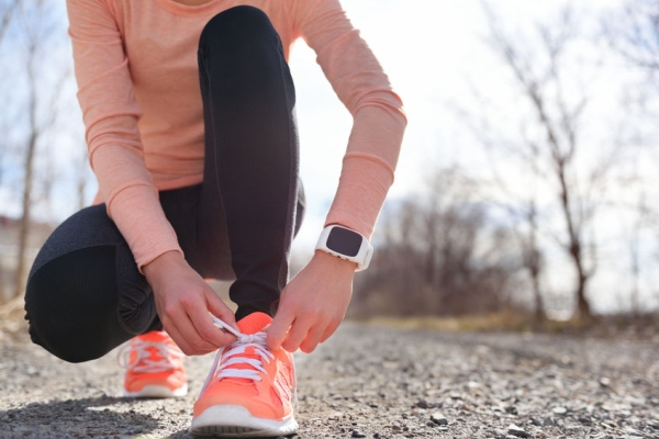 44400127 - running shoes and runner sports smartwatch. female runner tying shoe laces on running trail using smart watch heart rate monitor.