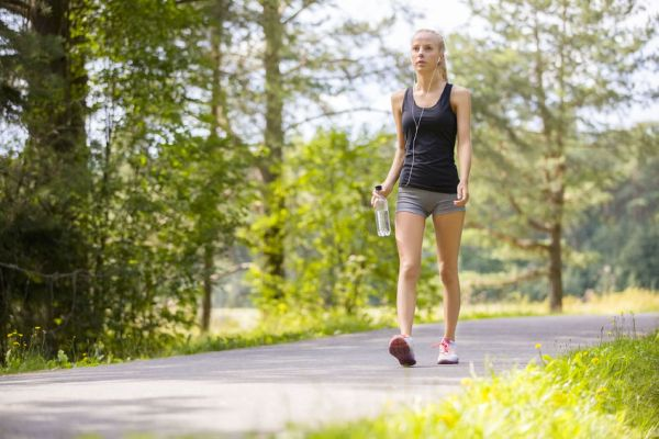 45840274 - beautiful young and fit blonde woman walking on trail in the woods. workout outdoor.