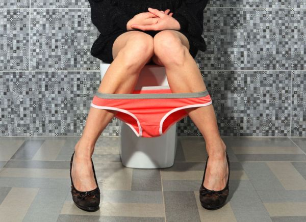 70451056 - part of the woman who sits on a toilet bowl