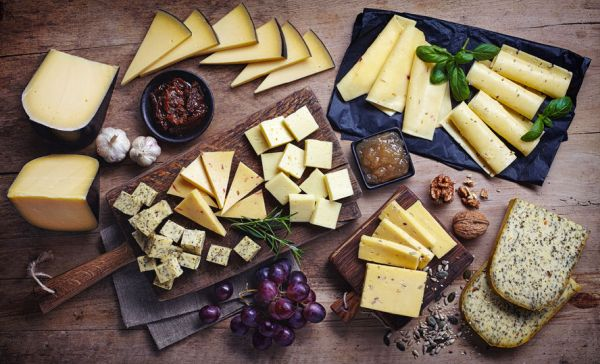 54328806 - cheese plates served with grapes, jam, figs, crackers and nuts on a wooden background, top view