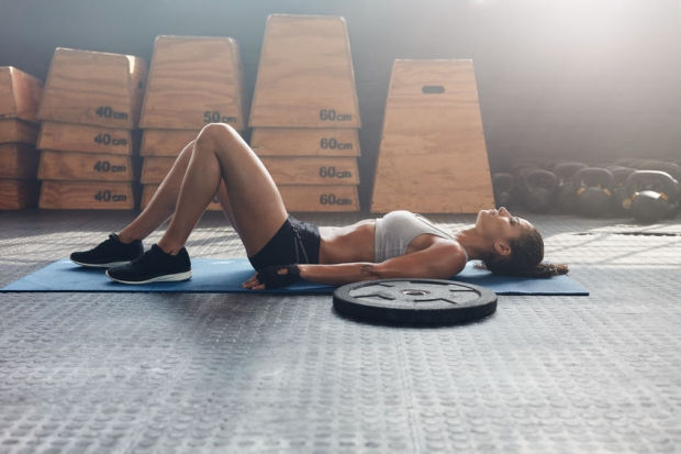 57563068 - side view shot of fitness woman resting on exercise mat with a heavy weight plate on floor. female athlete lying on her back after a gym workout