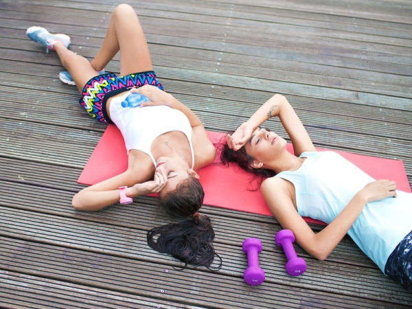 61863946 - two fit young women friends lying down tired after workout exercising in a park. active healthy lifestyle concept