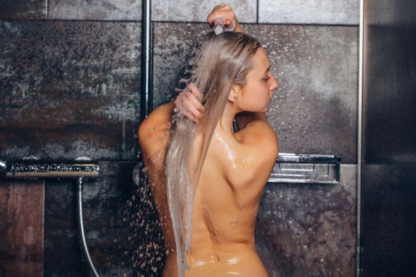 51936981 - beautiful woman standing at the shower. woman is washing her hair.