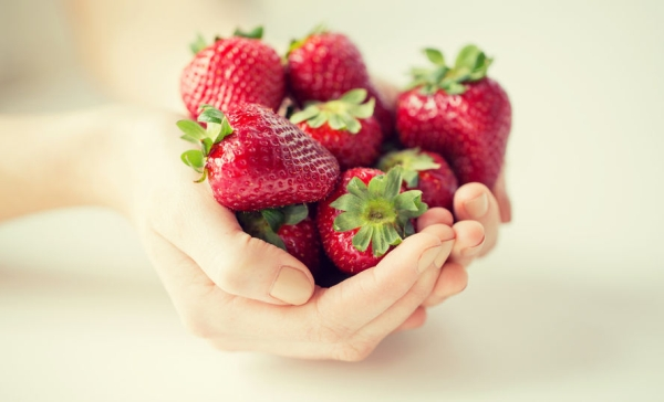 59328839 - healthy eating, dieting, vegetarian food and people concept - close up of woman hands holding strawberries at home