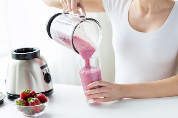53435597 - healthy eating, cooking, vegetarian food, dieting and people concept - close up of woman with blender and strawberries pouring milk shake to glass at home