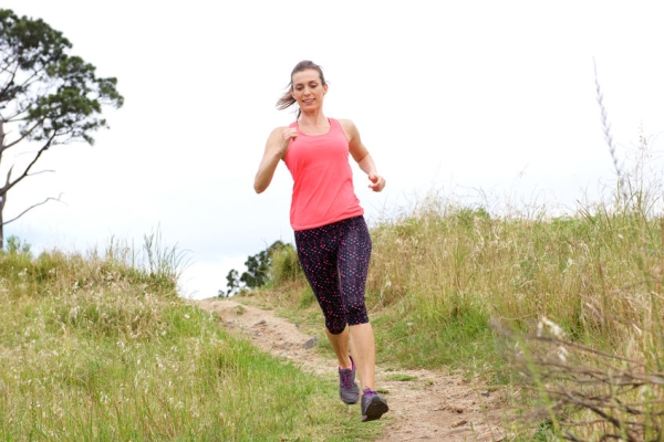 57021759 - full length portrait of sporty woman running on dirt path outdoors in park