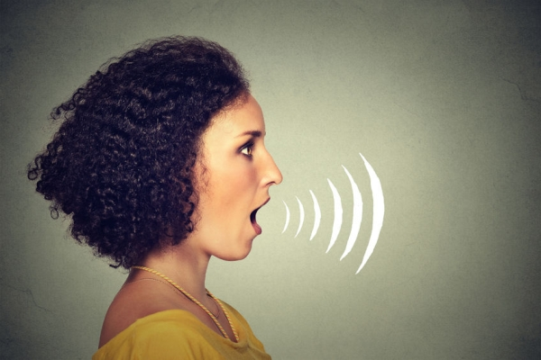 51742531 - side profile young woman talking with sound waves coming out of her mouth isolated on grey wall background. human face expressions