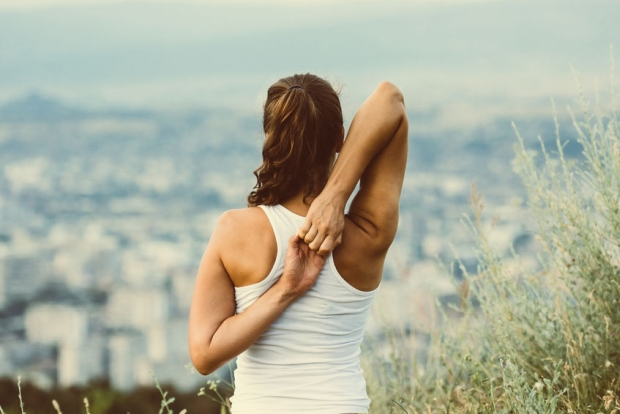 43663238 - young woman sits in yoga pose with city on background. freedom concept. calmness and relax, woman happiness. toned image