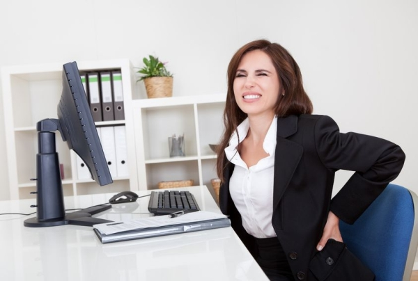 15179453 - young businesswoman having back pain while sitting at office desk
