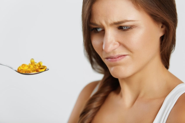 47894950 - diet concept. nutrition. vitamins. healthy eating, lifestyle. close up of woman with spoon full of fish oil omega-3 capsules. healthcare and beauty. vitamin d, e, a cod liver oil pills. supplements.