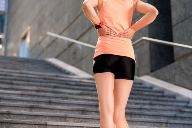 62790752 - back view of young woman in sportswear touching her lower back muscles by painful injury standing on the stairs.
