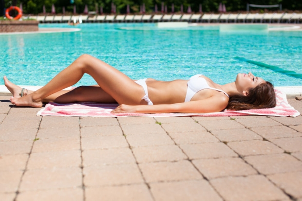 55366715 - beautiful woman relaxing in a pool in summer