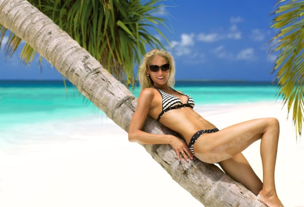 21201984 - beautiful model lying on the palm in bikini and sunglasses with perfectly shaped body