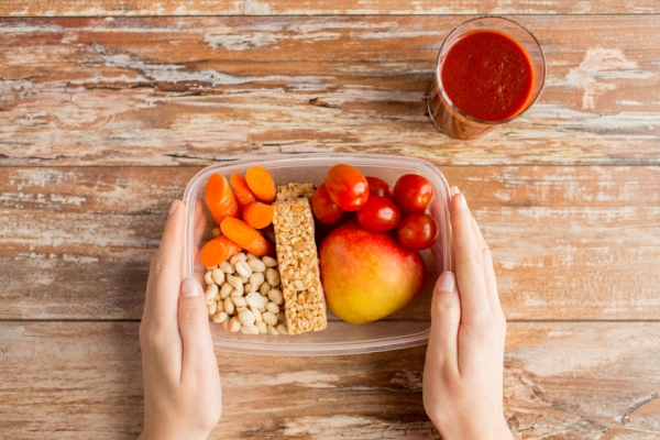 40525842 - healthy eating dieting and people concept  close up of woman hands with food in plastic container and fresh tomato juice at home kitchen