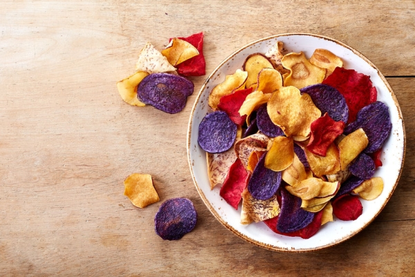 63450928 - bowl of healthy colorful vegetable chips on wooden background from top view