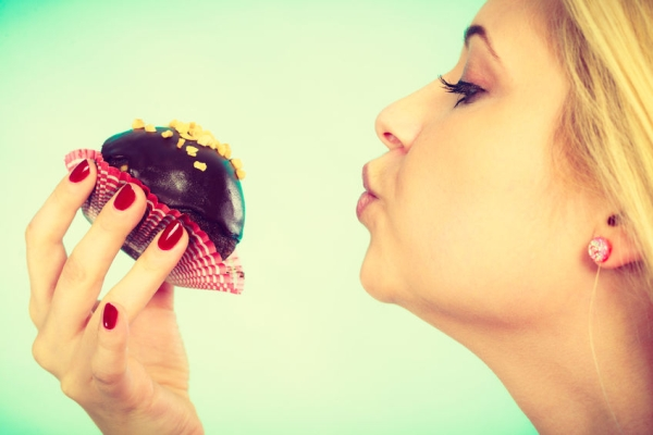 66304029 - diet, sweets, food concept. cute blonde attractive woman about to eat delicious chocolate cupcake, sending air kiss to her dessert