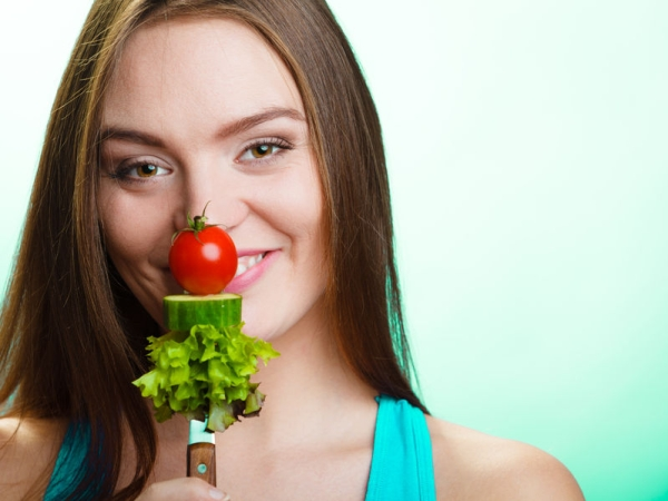 37923960 - diet and weight loss concept. funny girl fitness woman holding fork with fresh mixed vegetables on green blue background.