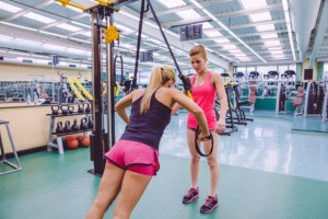 40908126 - female personal trainer teaching to woman in a hard suspension training with fitness straps on a fitness center